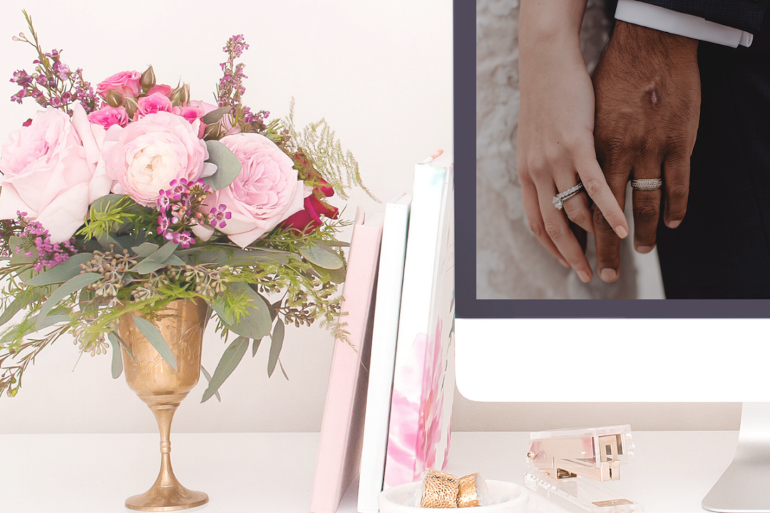 Desktop with wedding photo of bride and groom holding hands, flowers on the desk