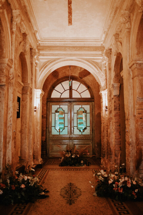 Brody Studios, Emphasizing the Wedding doors and entrance with florals in this rustic venue Budapest
