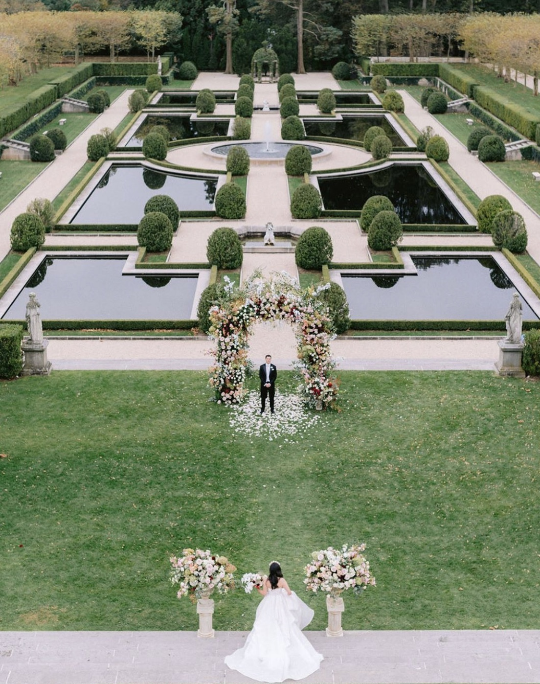 First-look-photography-outdoor-oheka-castle-new-york-greg-finck-photography-at manicured-gardens-groom-waiting-for bride-under-floral-wedding-archway