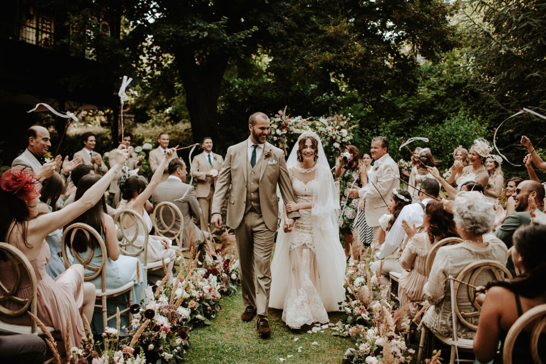 Outdoor Wedding ceremony in Budapest, newly married couple walking down the floral aisle with wedding guests applauding and cheering at dream wedding in Budapest