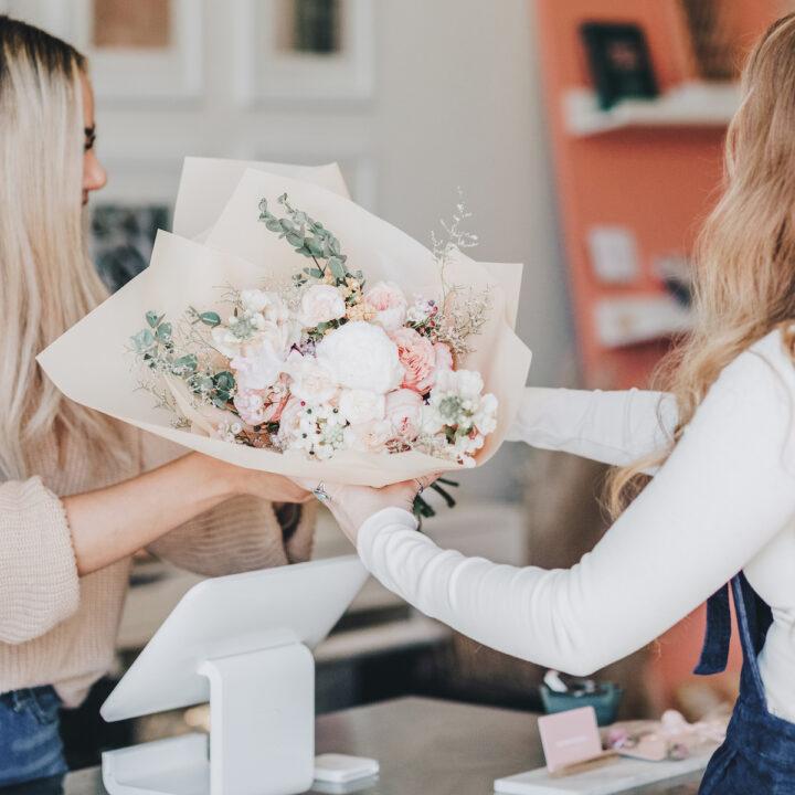 Florist giving wedding bouquet to wedding planner