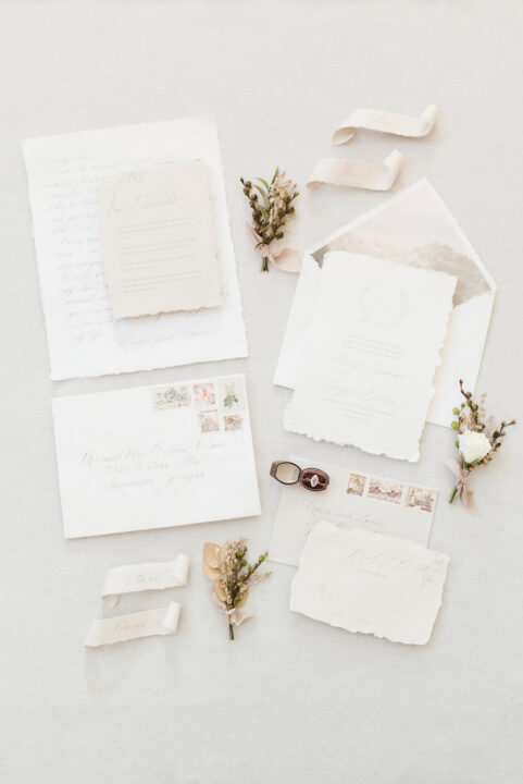 wedding invitations and save the date stationery flat lay with flowers and wedding ring
