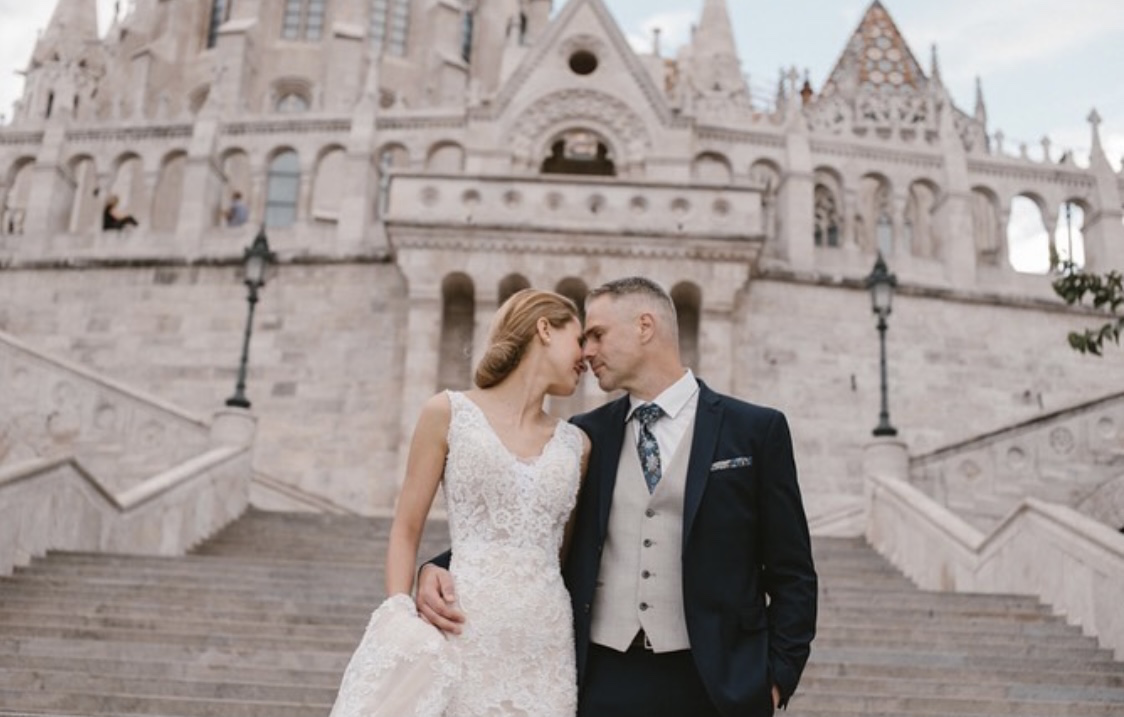 Destination wedding Budapest, with fairytale wedding portraits at Fisherman's Bastion Budapest, with Mathias Church in the background